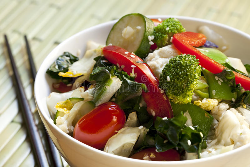 Stir-Fried Vegetables. Bowl of stir-fried vegetables topped with sesame seeds. With chopsticks. Delicious healthy eating royalty free stock images