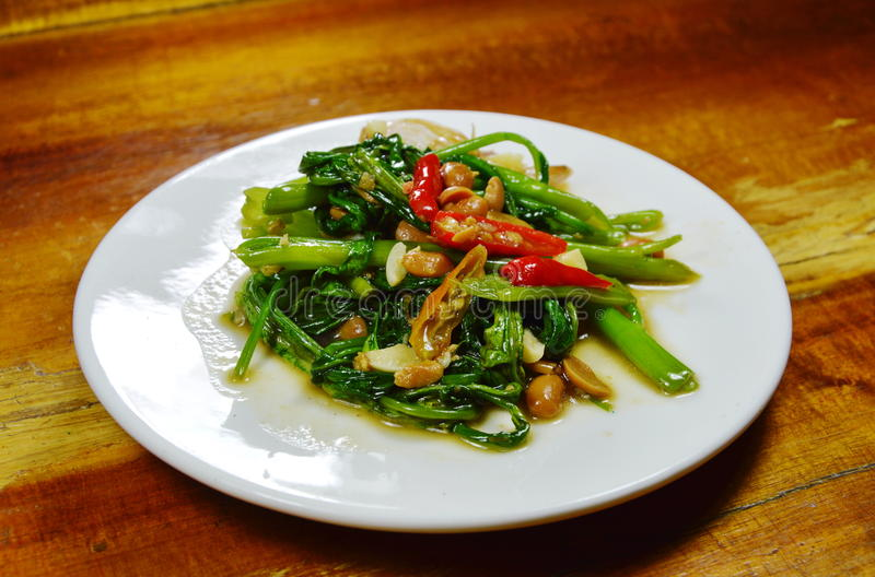 Stir fried water spinach with chili and soy bean paste on dish. Stir fried water spinach with chili and soy bean paste on white dish stock photos