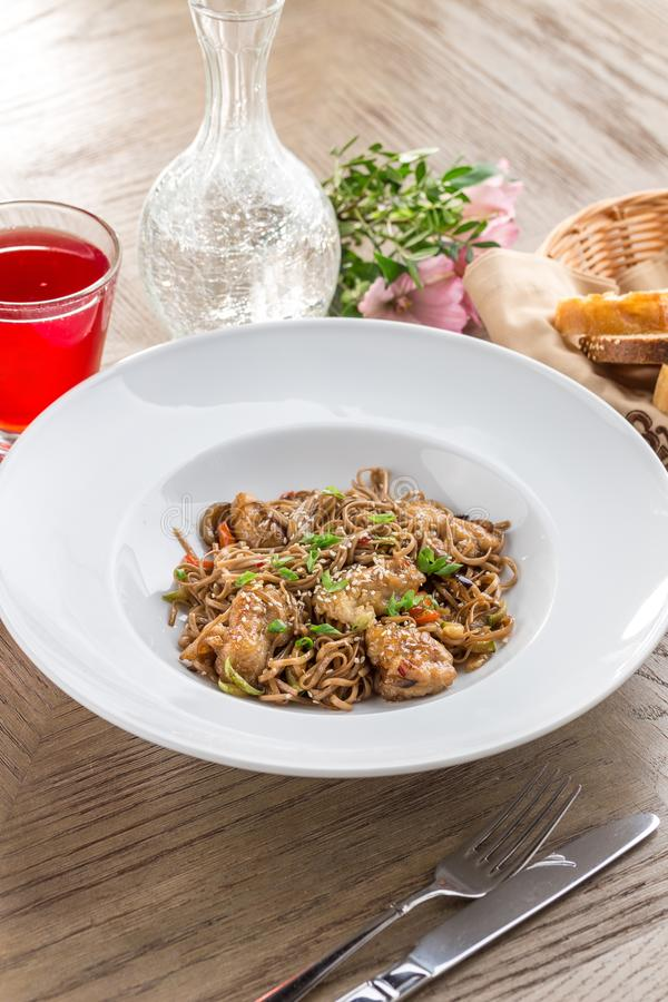 Stir fried yakisoba noodle with pork Asian food style with red drink on wooden table stock photo