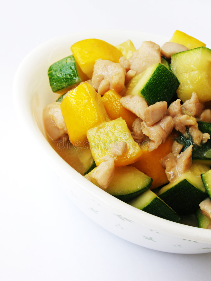 Stir fried zucchini & chicken. A simple yet tasty dish of stir-fried yellow and green organic zucchinis with small pieces of marinated chicken. Served in clean stock images