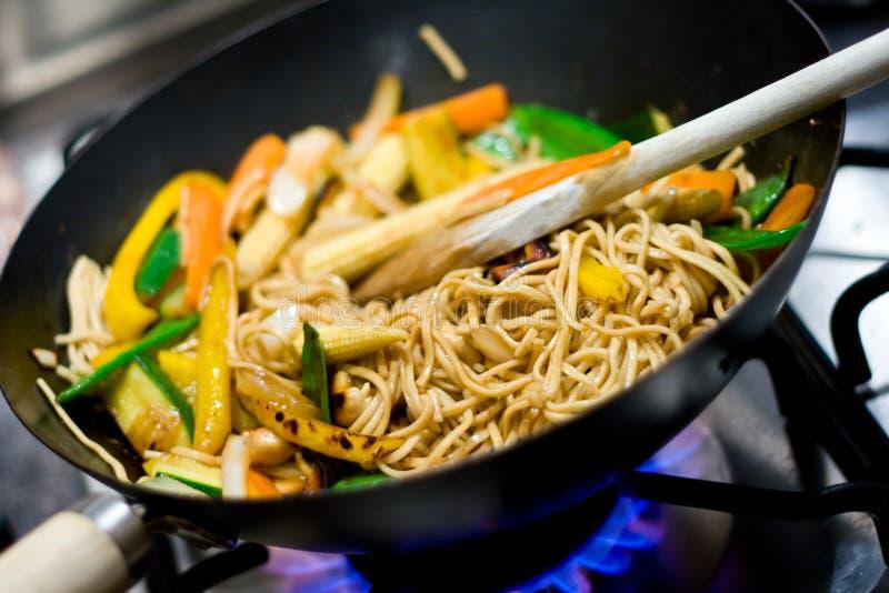 Stir-fry #4. Close-up of gas burner and wok with stir-fried vegetables stock image