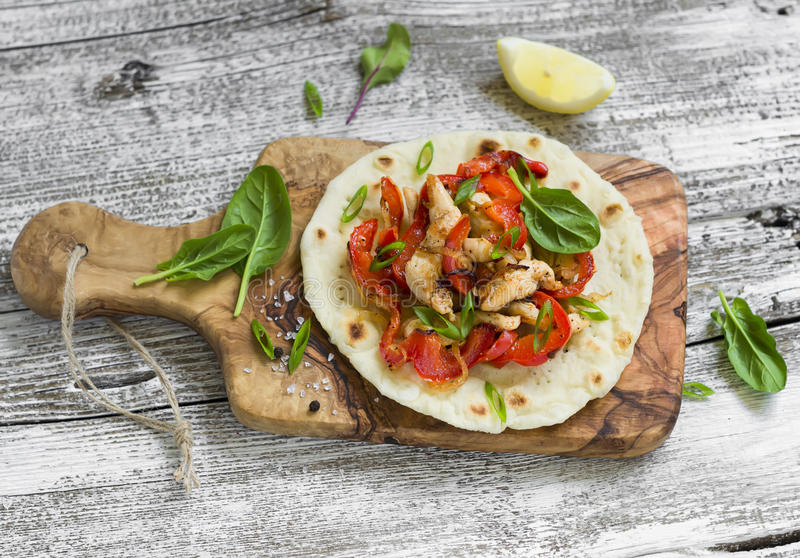 Stir fry of chicken breast and sweet red peppers on homemade tortillas. On a light wooden background royalty free stock photography