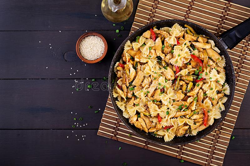 Stir fry chicken, pasta farfalle, zucchini, sweet peppers and green onion. stock photos