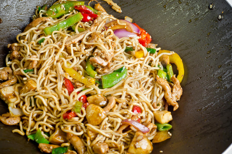 Stir fry noodle. With chicken in a wok pan royalty free stock photography