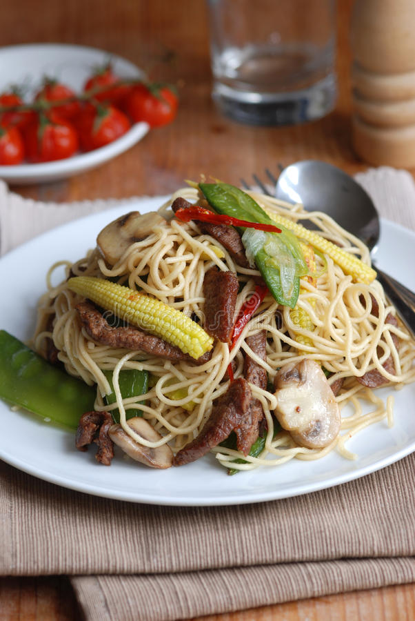 Stir-fry with noodles. Stir-fried pork with egg noodles on a plate royalty free stock images