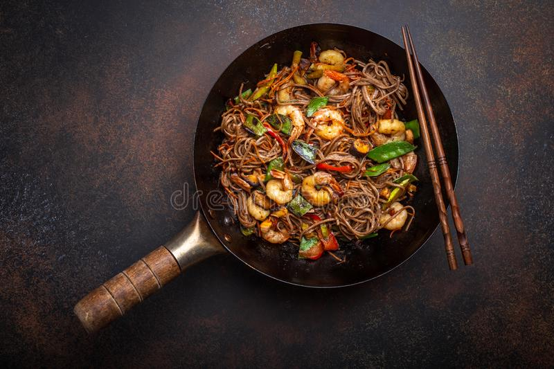 Stir fry noodles with shrimps and vegetables. Chinese soba stir-fry noodles with shrimps, vegetables in old rustic wok pan served on concrete background, close stock photo