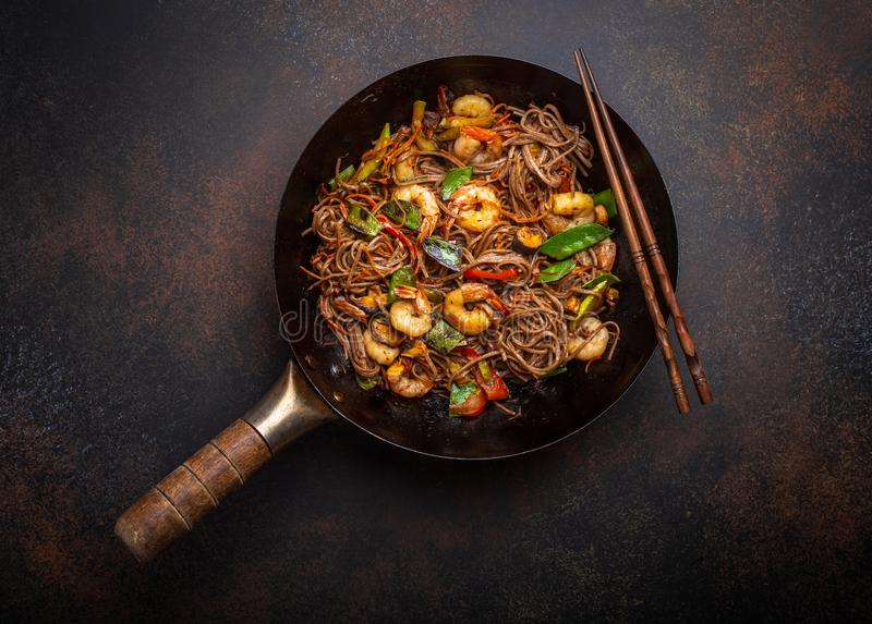 Stir fry noodles with shrimps and vegetables. Chinese soba stir-fry noodles with shrimps, vegetables in old rustic wok pan served on concrete background, close royalty free stock photography