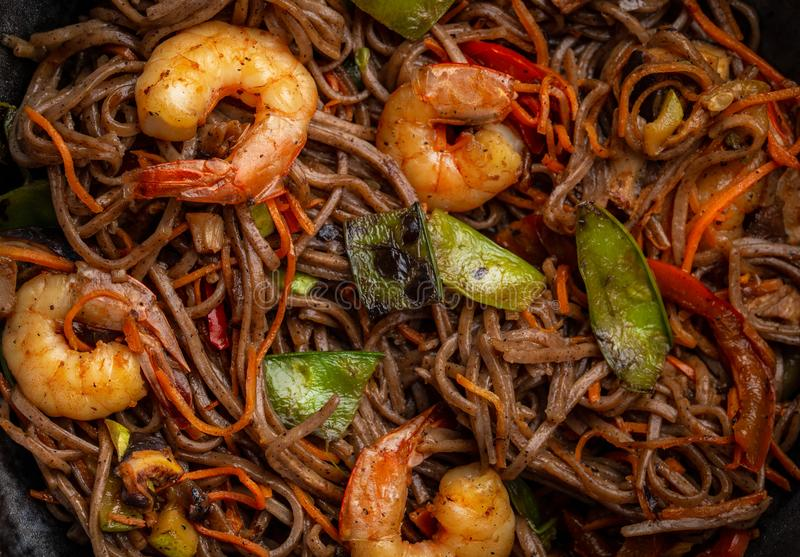 Stir fry noodles with shrimps and vegetables. Close-up of Chinese soba stir-fry noodles with shrimps and vegetables, carrot, green beans, mushrooms, pepper, top stock image