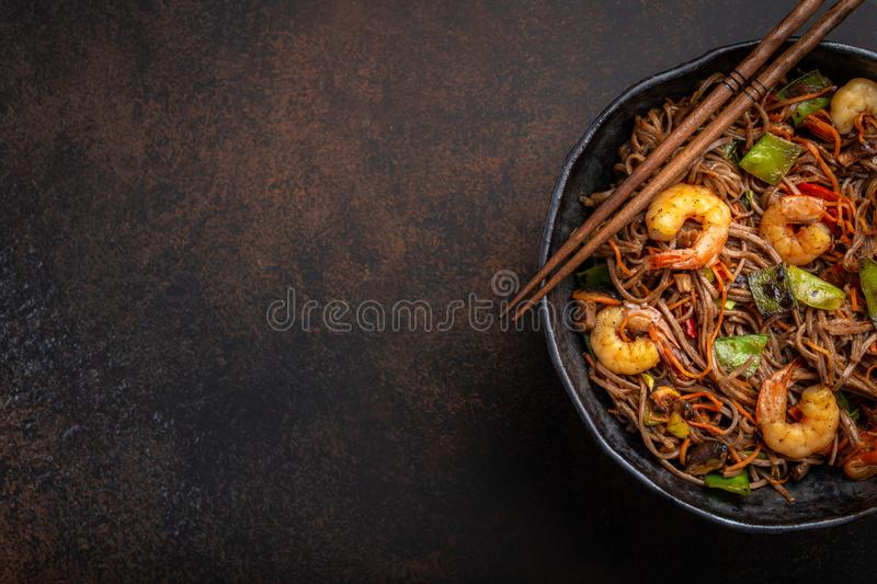 Stir fry noodles with shrimps and vegetables. Close-up of Chinese soba stir-fry noodles with shrimps, vegetables in rustic ceramic bowl pan served on concrete royalty free stock images