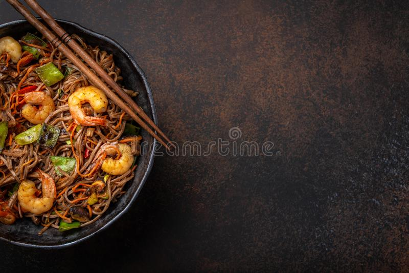 Stir fry noodles with shrimps and vegetables. Close-up of Chinese soba stir-fry noodles with shrimps, vegetables in rustic ceramic bowl pan served on concrete stock photography
