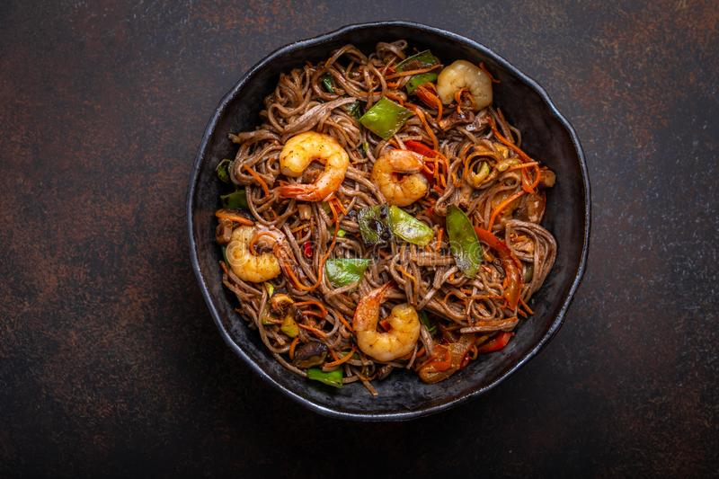 Stir fry noodles with shrimps and vegetables. Close-up of Chinese soba stir-fry noodles with shrimps, vegetables in rustic ceramic bowl pan served on concrete royalty free stock image