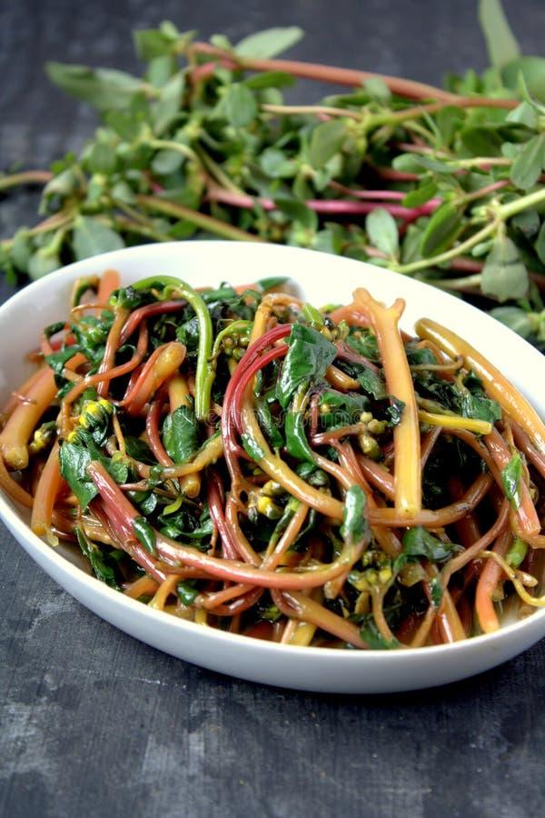 Stir Fry pigweed. Stir Fried pigweed or Portulaca oleracea or purslane, verdolaga, pigweed, little hogweed, red root, pursley, and moss rose. Known as Lonsiman stock photo