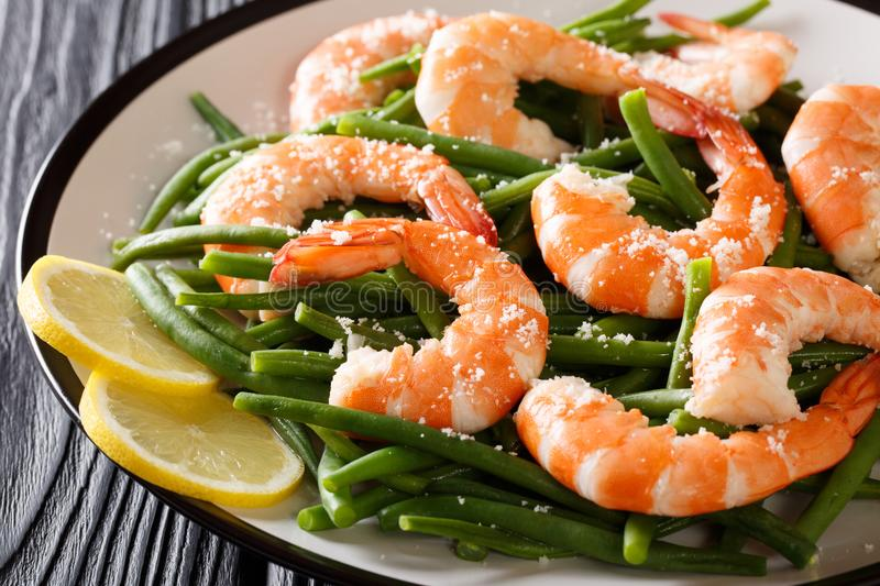 Stir fry prawns with green beans, cheese and lemon close-up on a. Plate on the table. horizontal stock photo
