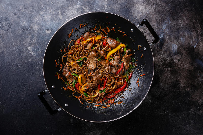 Stir-fry soba noodles with beef. And vegetables in wok pan on dark background stock photo