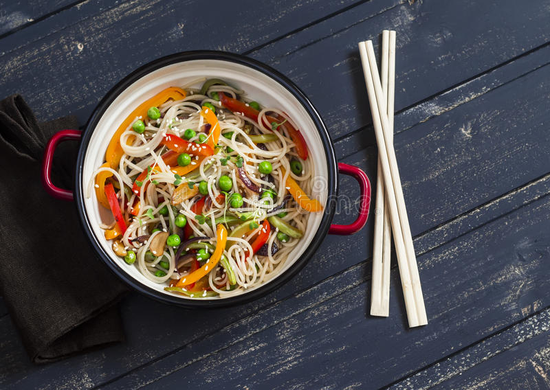 Stir fry vegetable with rice noodles in an enamel pot. On dark wooden background royalty free stock photos