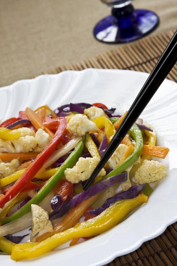 Stir fry vegetables. Vegetables stir fry. Red, yellow, green pepper, cauliflower, cabbage, carrots. Focus around chopsticks stock image