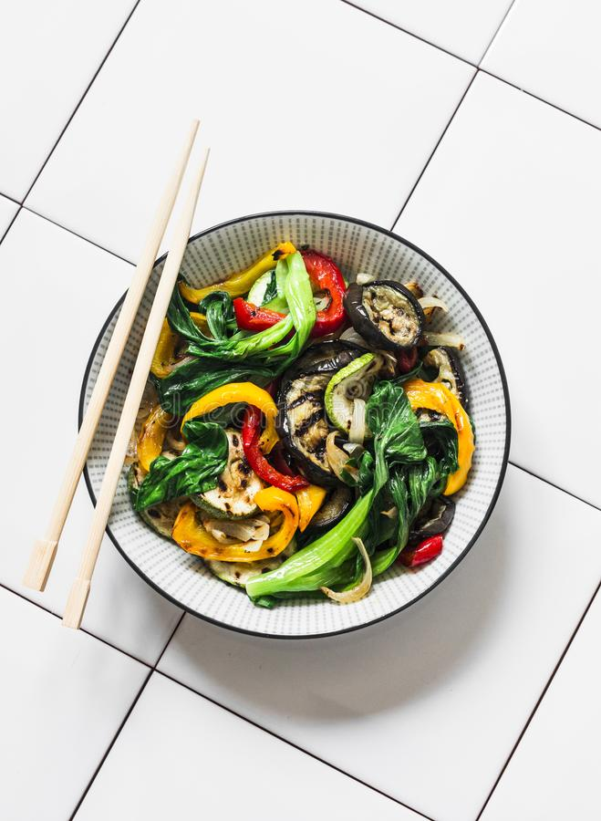 Stir fry vegetables in asian style. Quickly roasted wok vegetables - bok choy, eggplant, bell pepper, zucchini on a light royalty free stock photography