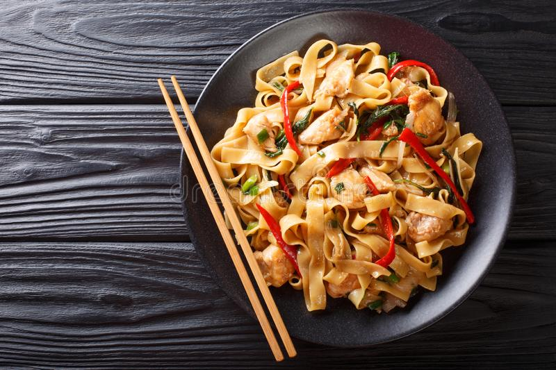 This stir-fry of wide rice noodles with chicken and fresh basil in a spicy, sweet and tangy sauce  close-up on a plate. horizontal stock image