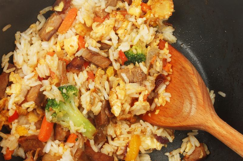 Stir fry in a wok. Closeup of fried rice with egg, pork and vegetables in a wok with a wooden spoon stock image