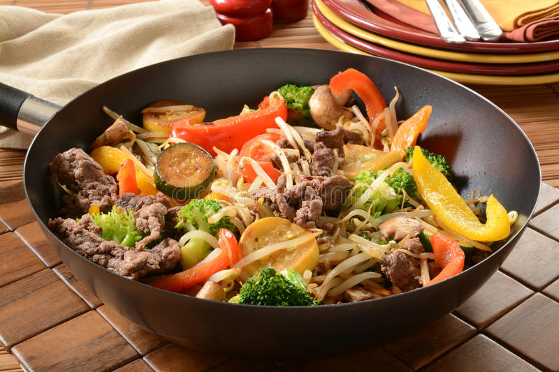 Stir fry in a wok. A healthy stir fry in a wok with serving plates royalty free stock photos