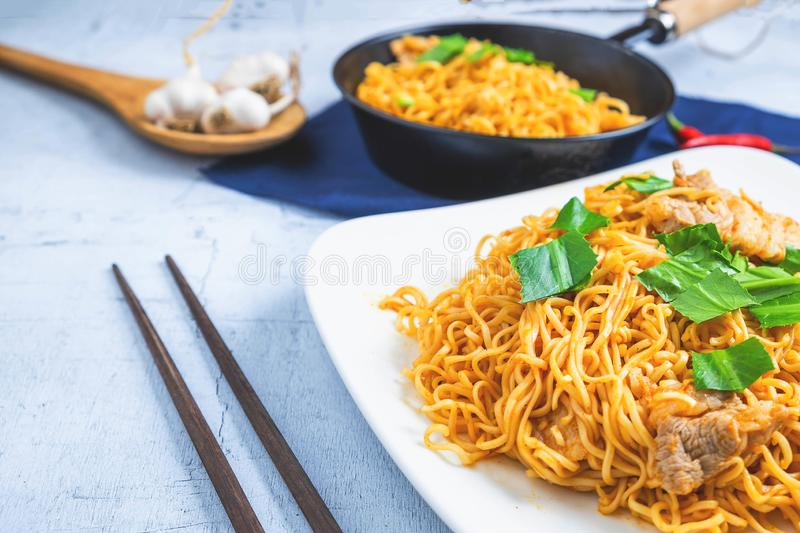 Stir noodles with vegetables in a white plate on a wooden floor stock images