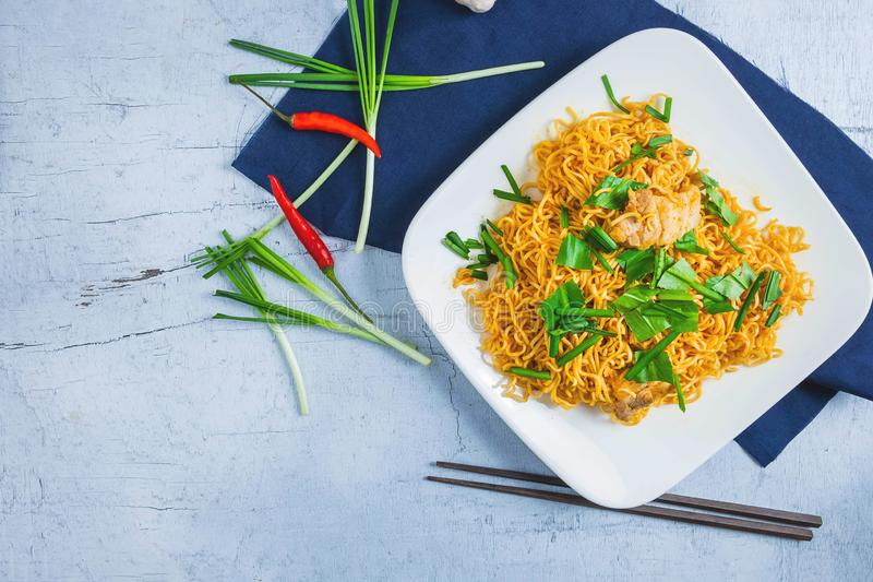 Stir noodles with vegetables in a white plate on a wooden floor royalty free stock image