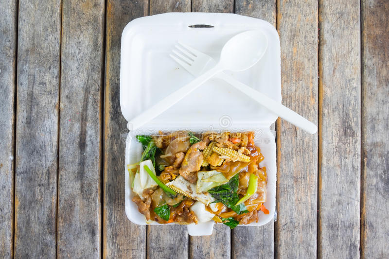 Stir soy sauce in foam box. Stir-fried Noodles in Sweet Soy Sauce with Pork (Pad See-Ew) in foam box royalty free stock image