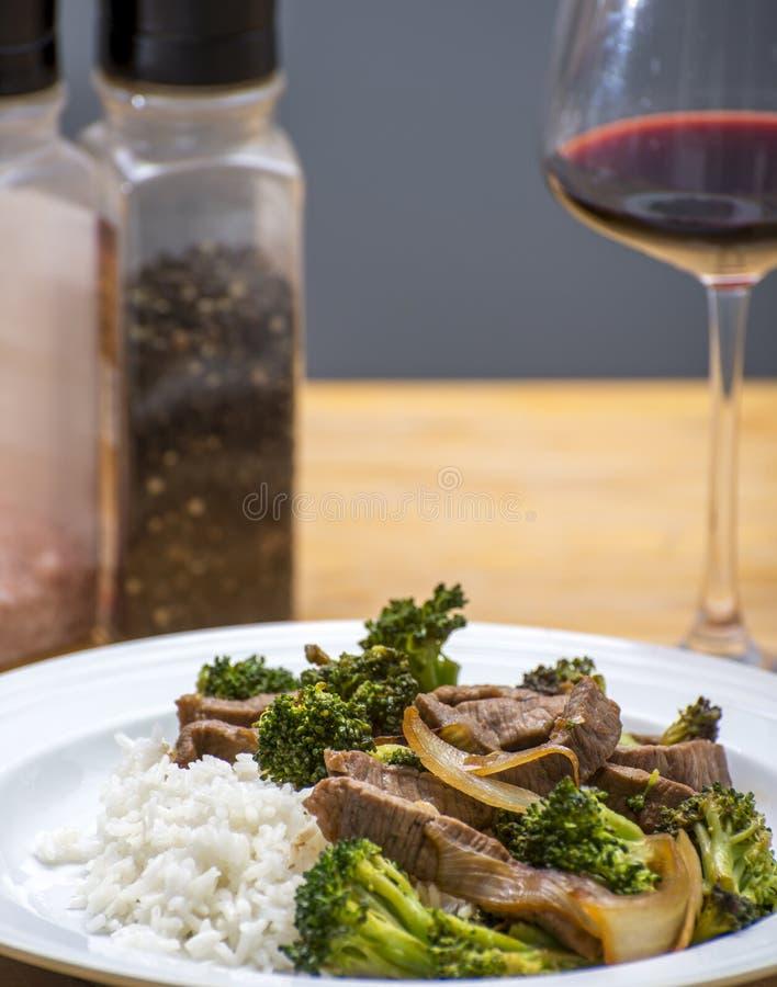 Stirfry cucinato dei broccoli e del manzo servito su riso con le spezie di vetro di vino nel fondo fotografia stock libera da diritti
