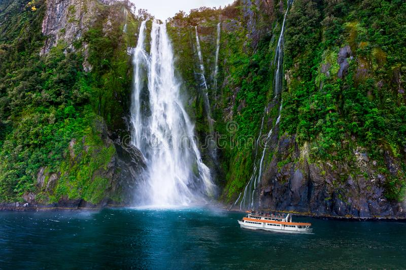 Stirling Falls at Milford Sound, New Zealand. Stirling Falls at Milford Sound in South Island of New Zealand. Tourist ferry approaching Stirling Falls, the stock photography