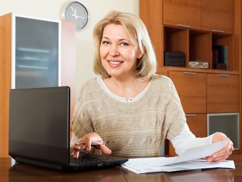 Stirriga finansiella dokument för mogen kvinna arkivbilder