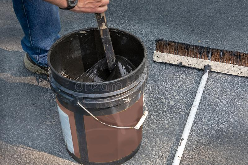 Stirring can of asphalt before pouring on driveway. Do it yourself home maintenance. Driveway resealing repair. Stirring sealant before using on asphalt driveway stock photography