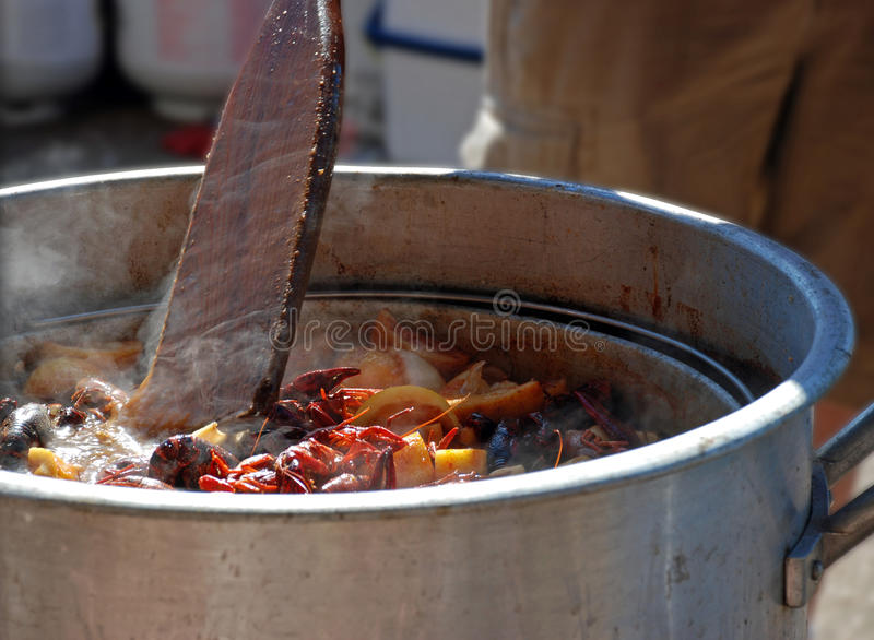 Stirring Crawfish. A cook stirs boiling hot crawfish, lemon wedges and seasonings with an oar at a low country seafood feast stock photo