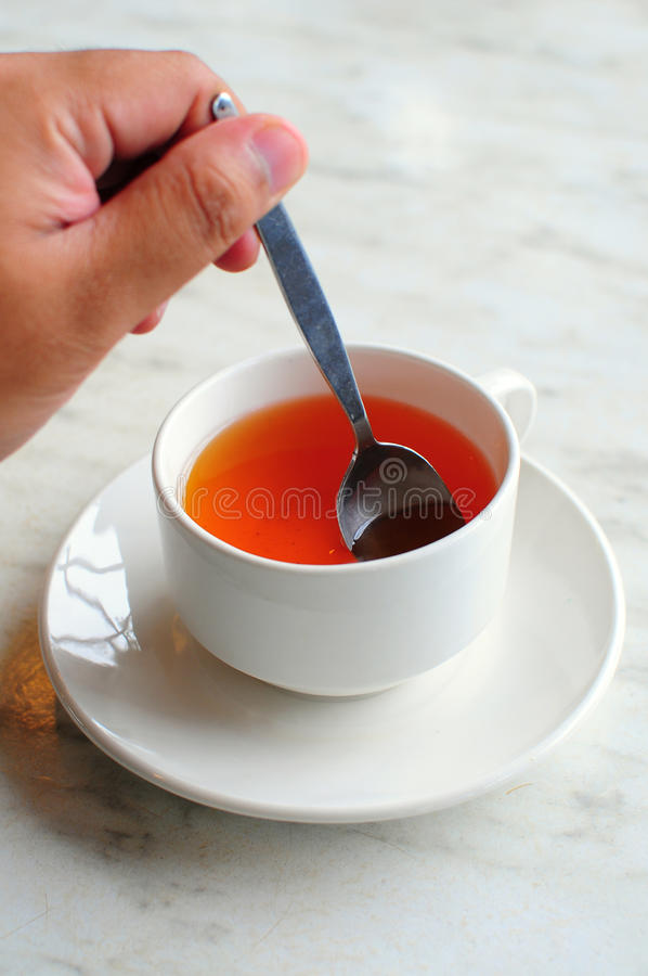 Stirring a cup of tea. A hand stirring a cup of tea with left hand stock images
