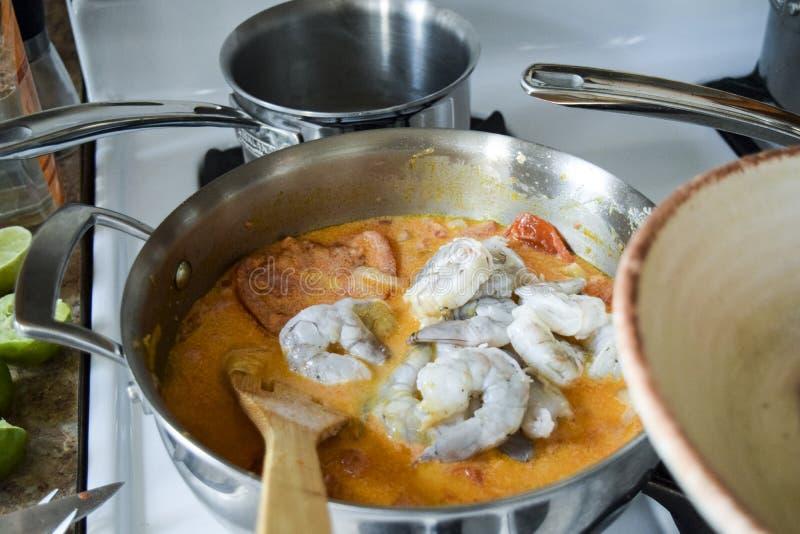 Stirring raw shrimp into Brazilian stew royalty free stock image