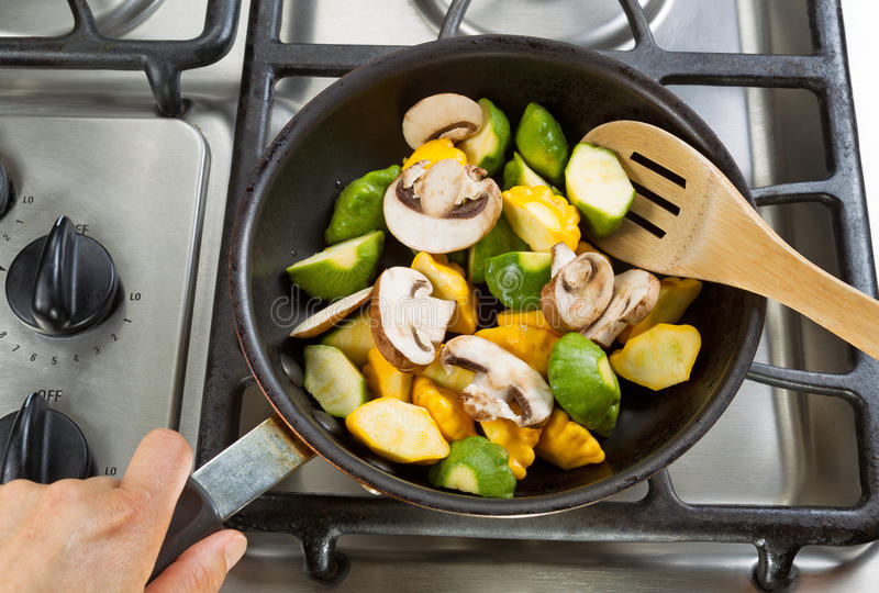 Stirring vegetables in Frying Pan with wooden spoon. Close up of hand holding frying pan, focus on food, while stirring vegetables with wooden spoon stock image