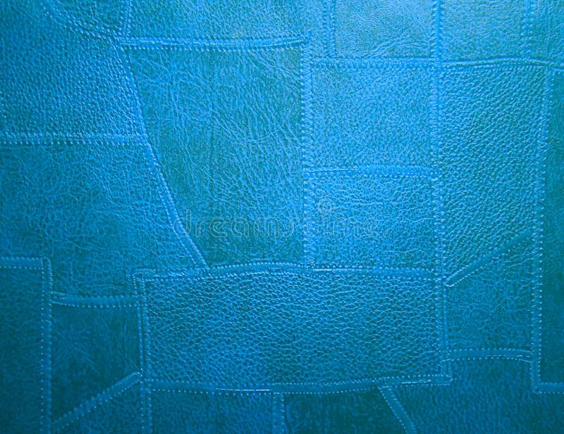 Stitched leather texture. Irregular shaped pieces of leather stitched together and colored blue. Texture or background, or wallpaper stock photos