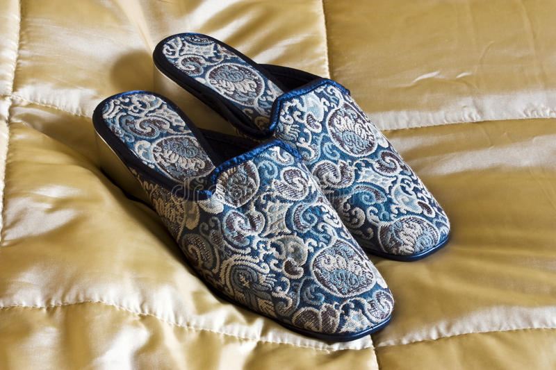 Embroided slippers. Embroidered ladies slippers on a satin bedspread stock images