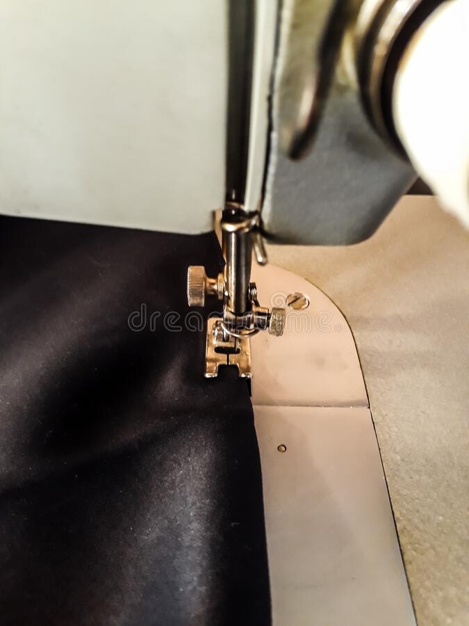 Stitching, vertical photo - the foot of a sewing machine on a black cloth, a straight line stock image