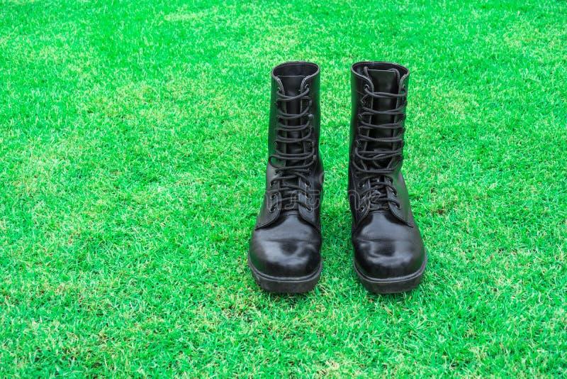 stivale di combattimento nero sul campo di erba verde immagine stock