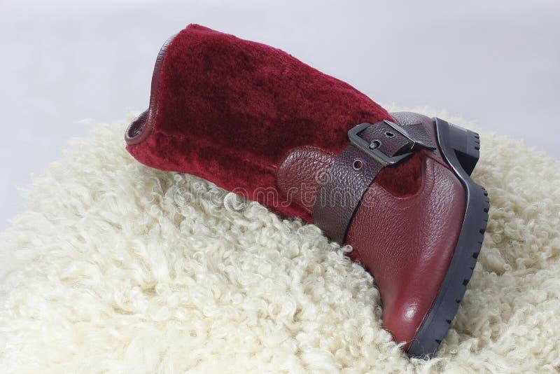 Stivali caldi messi su una pelle di pecora fotografia stock