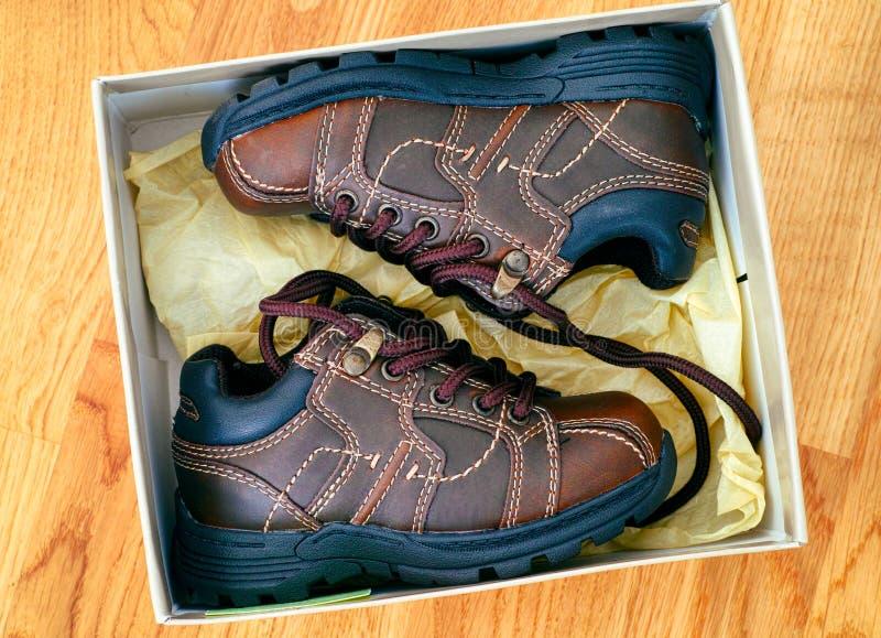 Stivali del bambino in scatola sul pavimento di parquet immagini stock