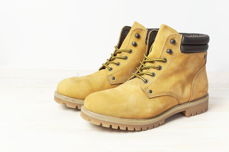 Stivali del lavoro degli uomini gialli dal cuoio naturale del nubuck su fondo bianco di legno Scarpe casuali d'avanguardia, stile immagine stock libera da diritti