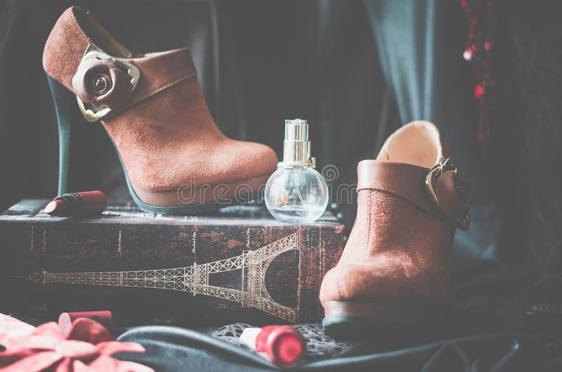 Stivali della caviglia, scarpe, le scarpe delle donne, supporto, piedistallo, rossetto, profumo, bottiglia, vetrina, rosso, proge fotografia stock libera da diritti