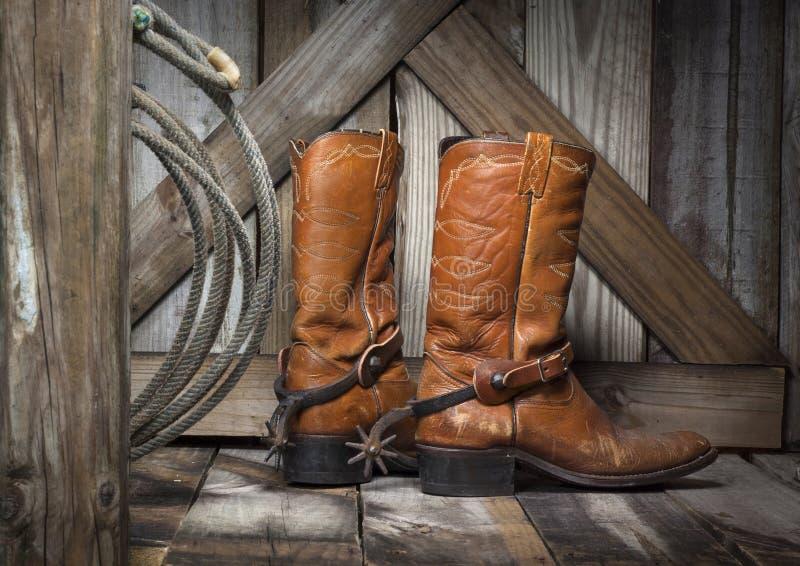 Stivali di cowboy su un portico del paese anziano fotografie stock libere da diritti