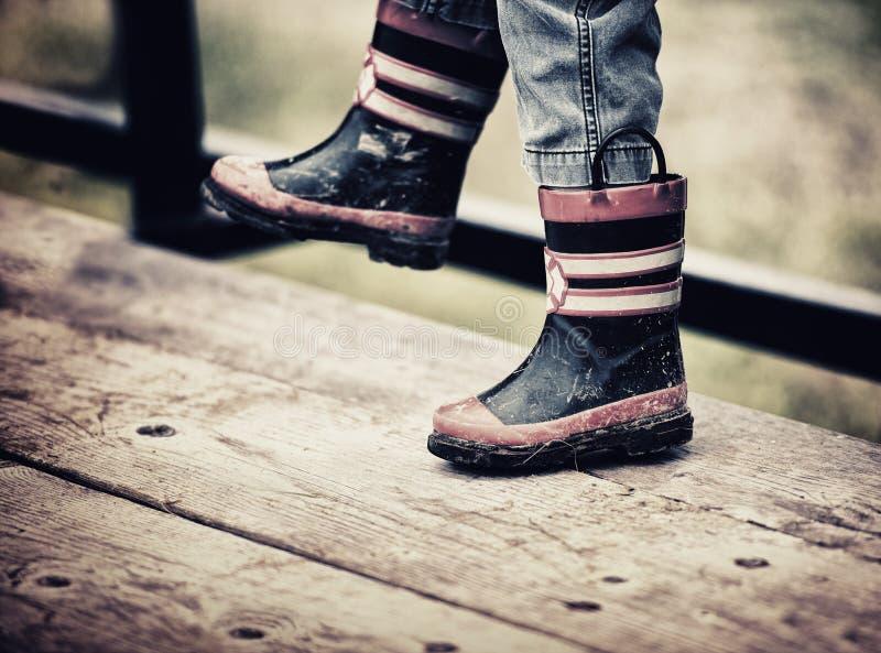 Stivali di pioggia d'uso del vigile del fuoco del giovane ragazzo fotografie stock libere da diritti