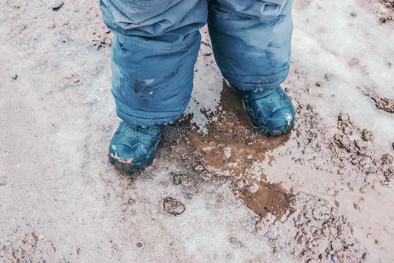Stivali di pioggia del bambino all'aperto nell'azione fotografia stock