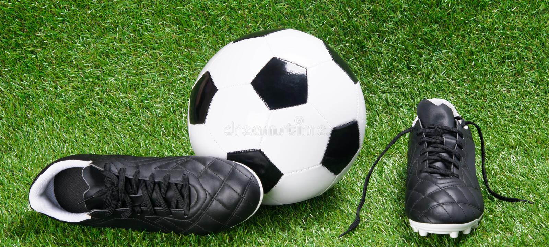 Stivali e palla di calcio per calcio, contro lo sfondo di erba fotografie stock libere da diritti