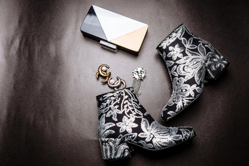 Stivali neri della caviglia con i talloni spessi decorati con i fiori ricamati con gli zecchini d'argento e una frizione e fibule fotografie stock libere da diritti