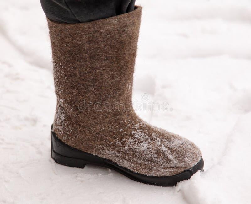 Stivali sui piedi di un uomo nell'inverno fotografie stock