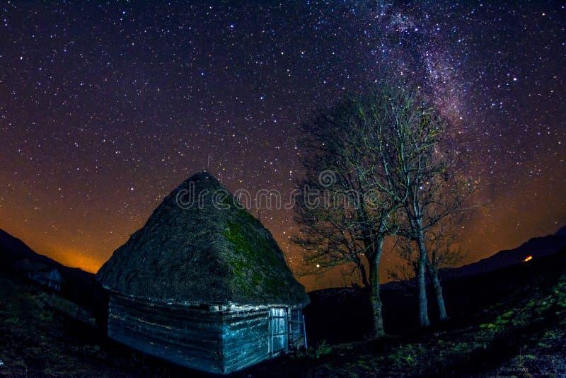 Stjärnabildandet för mjölkaktig väg som ses på en klar natt nära en gammal övergiven by med lantliga konstruktioner royaltyfria bilder